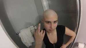 Marissa shaving her head with a razor