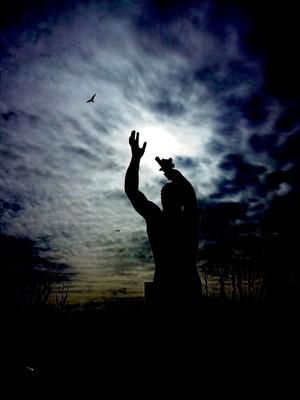 Estatua brazos en alto frente al sol con aves por ahi