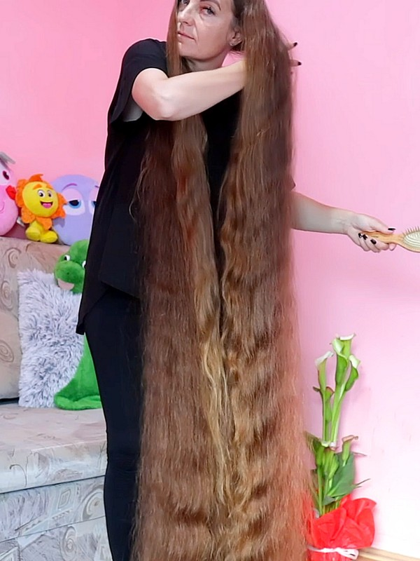 VIDEO - Hair so long that she has to stand in the sofa