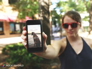 Woman showing her iPhone Mockup (PSD)