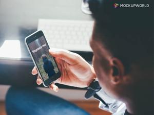 Man holding iPhone Mockup (PSD)