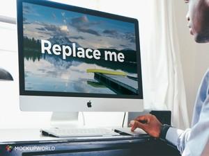 Man working on an iMac Mockup (PSD)