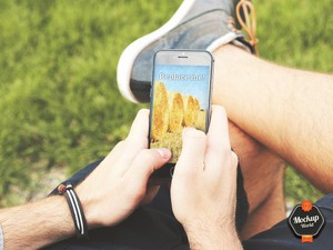 Guy holding an iPhone in the Park Mockup (PSD)
