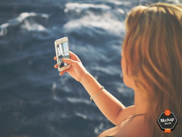 Woman with iPhone on windy Beach Mockup (PSD)