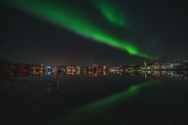 Northern lights over Reykjavik city, Iceland