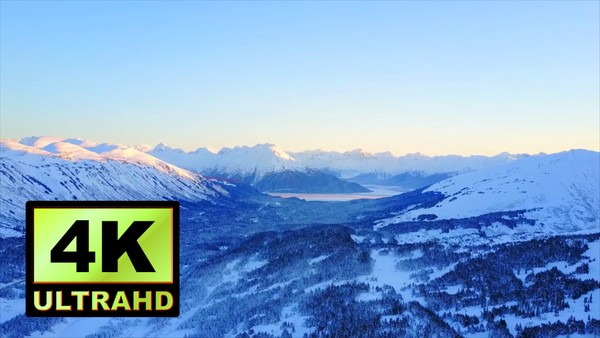 01715_aerial drone footage of snowed mountain range and pine forests in Alaska_4K UltraHD Version