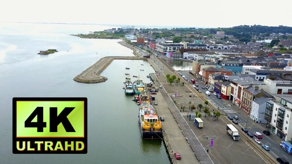 01778_aerial drone footage of small riverside town with harbor in Ireland_4K UltraHD Version
