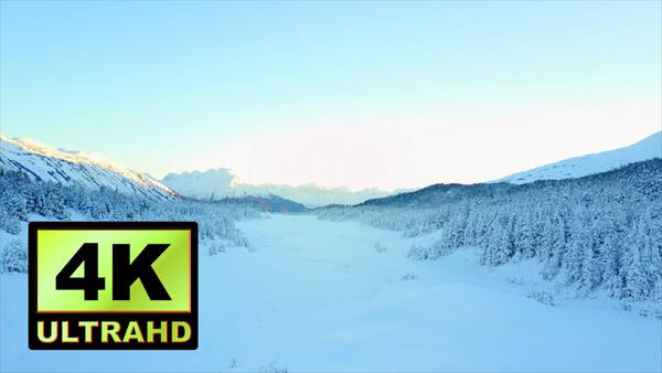 01712_aerial drone footage of a snowed frozen river and forest in Alaska_4K UltraHD Version